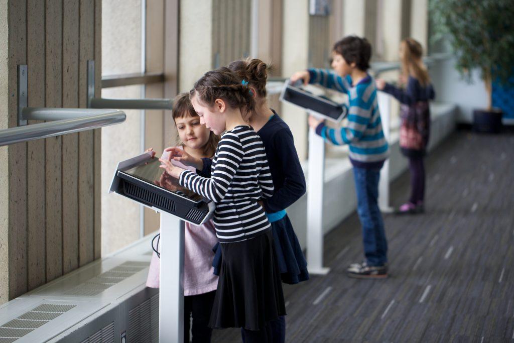 Kids looking on a tablet at Observatoire de la Capitale